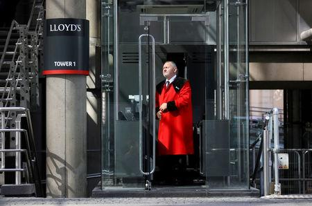 FILE PHOTO: A doorman stands outside Lloyds of London's headquarters in the City of London
