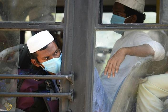 Men in facemasks wait on a bus taking them to a quarantine facility after they attended an Islamic gathering which has turned out to be a hotspot for Coronavirus infections in Nizamuddin, New Delhi (AFP Photo/Sajjad HUSSAIN)