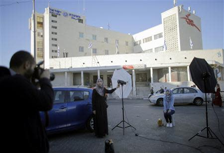 Palestinian students hold a photo shoot in front of a post office building in East Jerusalem
