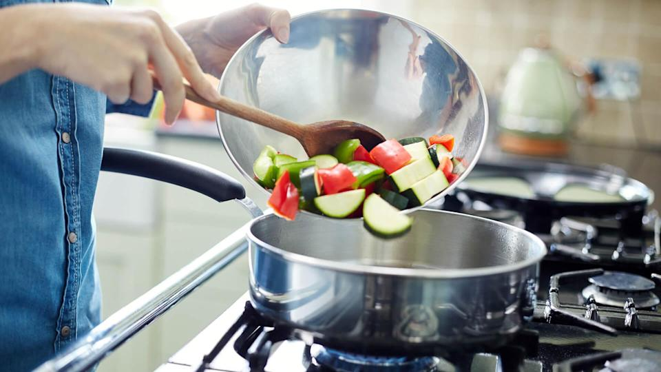 Midsection of woman adding fresh chopped vegetables in saucepan.