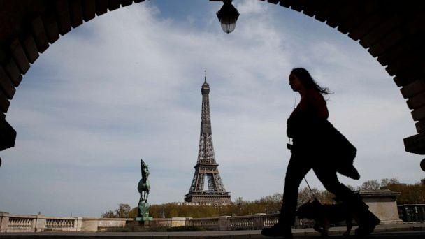 PHOTO: A woman walks her dog on a bridge with the Eiffel tower in the background in Paris, France, on April 7, 2020, during a nationwide confinement to counter the novel coronavirus. (Christophe Ena/AP)