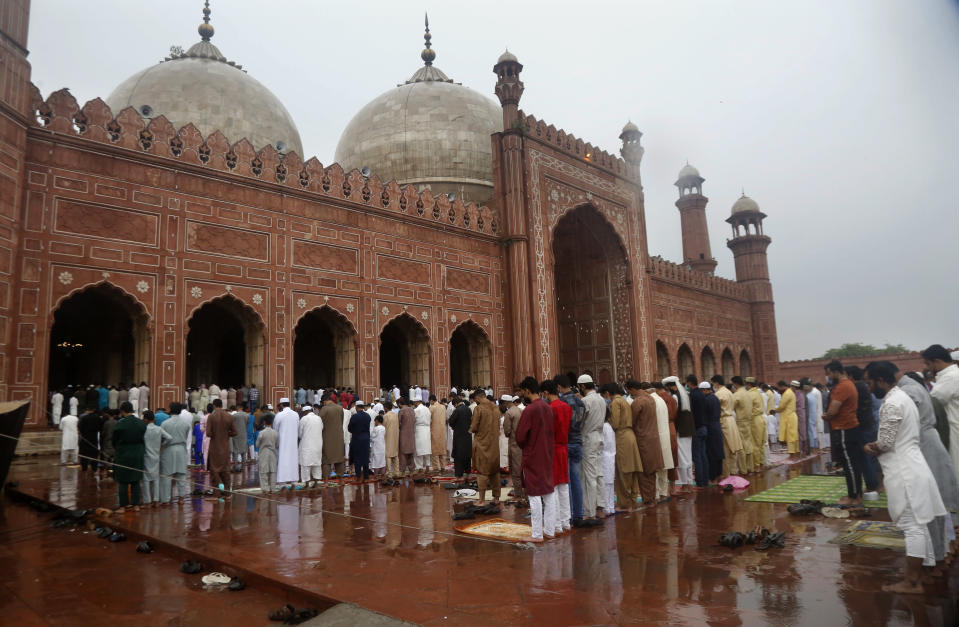 Muslims perform an Eid al-Fitr prayer at historical Badshahi mosque, in Lahore, Pakistan, Thursday, May 13, 2021. Millions of Muslims across the world are marking a muted and gloomy holiday of Eid al-Fitr, the end of the fasting month of Ramadan, a usually joyous three-day celebration that has been significantly toned down as coronavirus cases soar. (AP Photo/K.M. Chaudary)