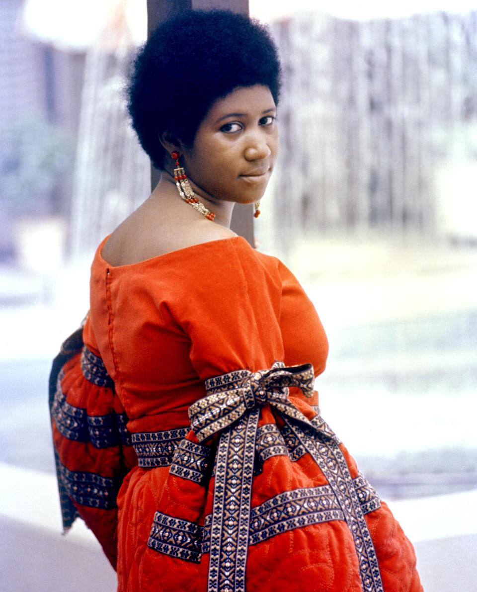 <p>Aretha Franklin wears a vibrant orange off-the-shoulder dress, matching bead earrings, and an Afro. (Photo by Michael Ochs Archives/Getty Images) </p>