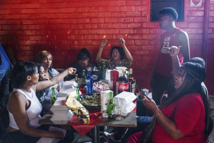 <p>Some teenagers during a braai, at Mzoli's Butchery, eating and drinking alcohol. Alcoholism combined with the quantity and low quality of food has increased the rate of obesity among young people. An example of the evolution of globesity is South Africa, with an obesity rate nearly double the global average and on its way to becoming one of the world's fattest nations. (Photograph by Silvia Landi) </p>