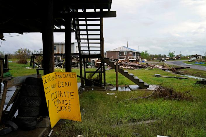 Storm clouds from Tropical Storm Nicholas are seen on Sept. 14, 2021, behind homes of the vanishing Native American community of Isle de Jean Charles, Louisiana, which was devastated by Hurricane Ida. (AP Photo/Gerald Herbert)