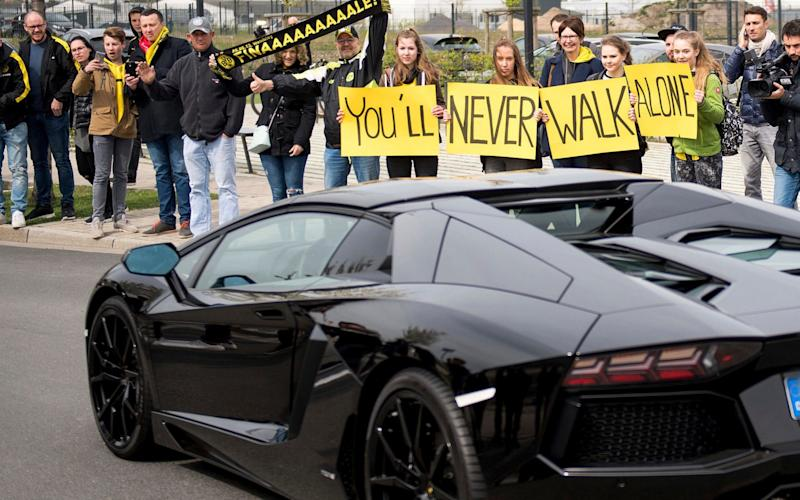 Fans show their support for Dortmund fans as player Pierre-Emerick Aubameyang leaves the training ground - Credit: Marius Becker/DPA/AP