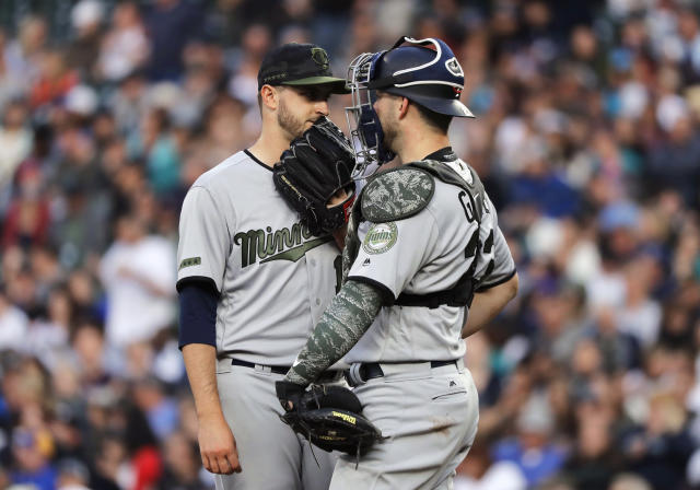 Minnesota Twins starting pitcher Jake Odorizzi, left, confers with catcher Mitch Garver during the fifth inning of the team's baseball game against the Seattle Mariners, Saturday, May 26, 2018, in Seattle. Both players were wearing special military-themed uniform gear intended to honor those who lost their lives while serving their country. (AP Photo/Ted S. Warren)