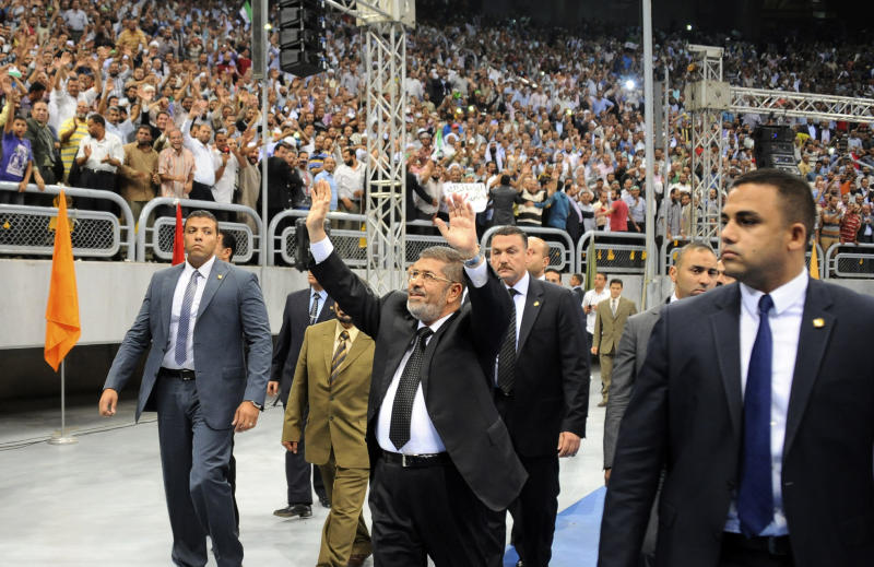 "In this image released by the Egyptian Presidency, Egyptian President Mohammed Morsi waves as he arrives at a rally called for by hardline Islamists loyal to the Egyptian president to show solidarity with the people of Syria, in a stadium in Cairo, Egypt, Sunday, June 15, 2013. Egypt's Islamist president announced Saturday that he was cutting off diplomatic relations with Syria and closing Damascus' embassy in Cairo, decisions made amid growing calls from hard-line Sunni clerics in Egypt and elsewhere to launch a ""holy war"" against Syria's embattled regime. (AP Photo/Egyptian Presidency)"