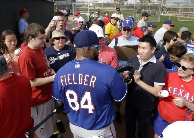 Texas Rangers' Prince Fielder signs autographs for fans after taking in his first workout with the team during spring training baseball practice, Wednesday, Feb. 19, 2014, in Surprise, Ariz. (AP Photo/Tony Gutierrez)