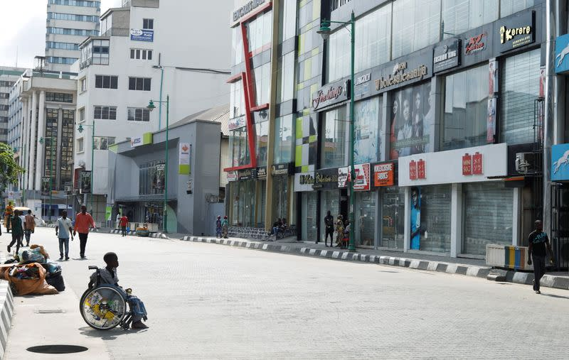People walk past shops remain closed in Lagos