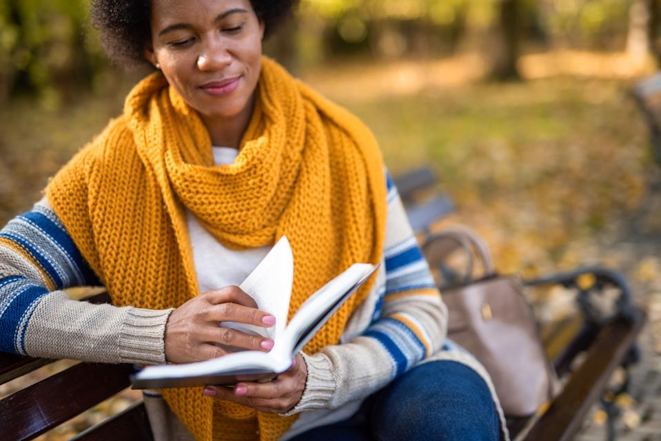 Mid adult African American woman sitting on bench and reading a book on autumn day in the park.