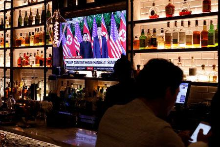 FILE PHOTO: A television screen at the Baro bar broadcasts the Singapore summit meeting between  U.S. President Donald Trump and North Korean leader Kim Jong Un, as customers sit at the bar in the Korea Town section of Manhattan, New York, U.S., June 11, 2018.  REUTERS/Andrew Kelly/Files