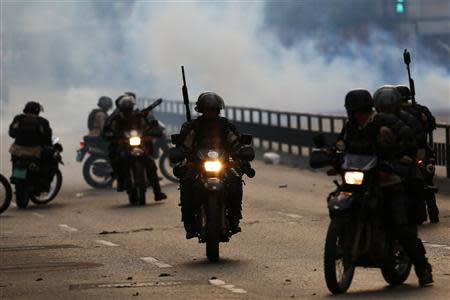 National police on motorcycles drive past a teargas cloud during a riot by anti-government protesters at Altamira square in Caracas March 10, 2014. REUTERS/Jorge Silva