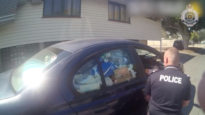 Plastic bottles and rubbish are seen filling up a side window of a car pulled over in Upper Mount Gravatt. The driver was pulled over because police said he couldn't see out his rear and side windows.