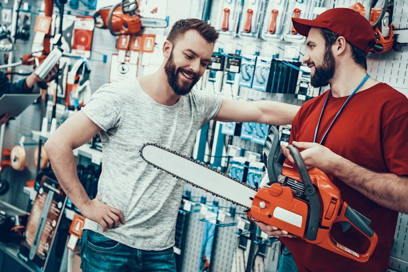Salesman with Customer in Power Tools Store. Salesman is Bearded Caucasian Man. Customer is Caucasian Young Man. Seller is Showing New Chainsaw to Client. People is Happy and Smiling.