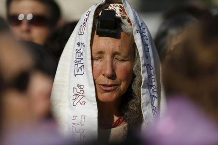 """A member of """"Women of the Wall"""" group wears a Jewish prayer shawl and Tefillin, leather straps and boxes containing sacred parchments, that Orthodox law says only men should don, during a monthly prayer session at the Western Wall in Jerusalem's Old City, in this May 10, 2013 file photo. REUTERS/Amir Cohen/Files"""