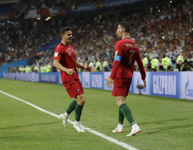 Portugal's Cristiano Ronaldo, right, celebrates with Portugal's Andre Silva after scoring during the group B match between Portugal and Spain at the 2018 soccer World Cup in the Fisht Stadium in Sochi, Russia, Friday, June 15, 2018. (AP Photo/Sergei Grits)