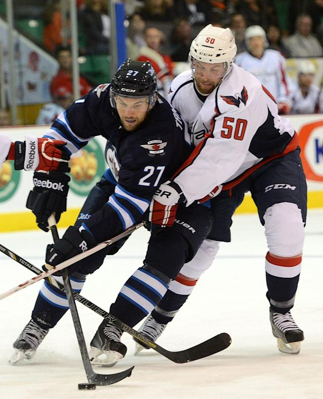 Washington Capitals' Dane Byers fights to get the puck from Winnipeg Jets' Eric Tangradi (27) during a preseason NHL hockey game on Saturday, Sept. 14, 2013, in Belleville, Ontario. (AP Photo/The Canadian Press, Sean Kilpatrick)