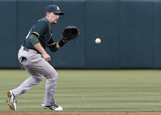 Oakland Athletics shortstop Jed Lowrie (8) fields a hit by Texas Rangers' Adrian Beltre (29) during the second inning of a baseball game, Monday, April 28, 2014, in Arlington, Texas. Lowrie would make the throw to first for the out. (AP Photo/Brandon Wade)