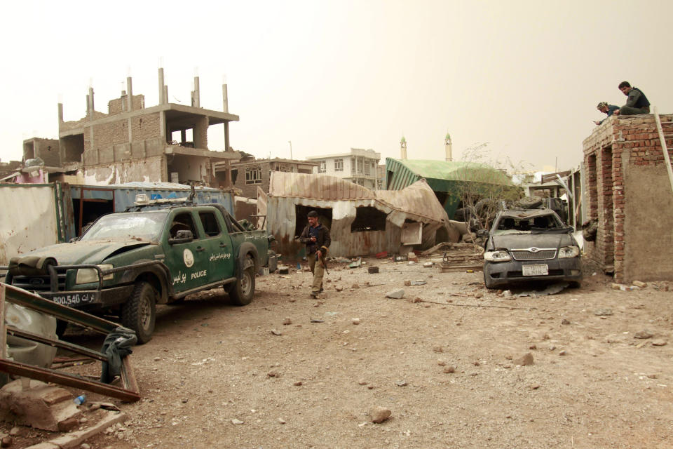Security officials inspect the site of a car bomb attack in Herat province, west of Kabul, Afghanistan, Saturday, March 13, 2021. A powerful car bomb killed numerous people and injured dozens more in Afghanistan's western Herat province, officials said Saturday. (AP Photo/Hamed Sarfarazi)