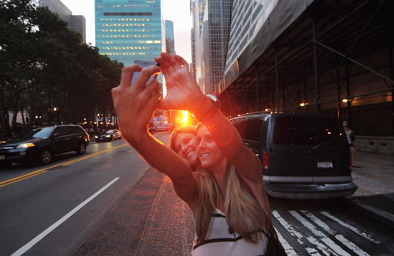 """Two women photograph themselves during the """"Manhattanhenge"""" sunset on July 13, 2011 in New York City. This semiannual occurrence was a half-sun Manhattanhenge, in which the setting sun aligns east-west with the street grid of the city. (Photo by Michael Loccisano/Getty Images)"""