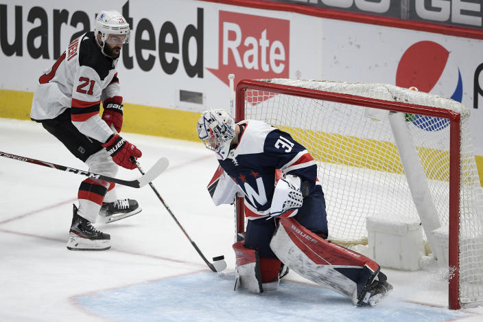 New Jersey Devils right wing Kyle Palmieri (21) skates with the puck towards Washington Capitals goaltender Craig Anderson (31) during the first period of an NHL hockey game, Sunday, Feb. 21, 2021, in Washington. (AP Photo/Nick Wass)