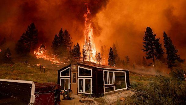 PHOTO: The Tamarack Fire burns behind a greenhouse in the Markleeville community of Alpine County, Calif., July 17, 2021. (Noah Berger/AP)