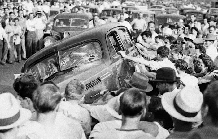 FILE - In this June 21, 1943 file photo, a mob turns over a car as police stand nearby, powerless to intervene, as race rioting between whites and blacks spread to many parts of Detroit. (AP Photo)