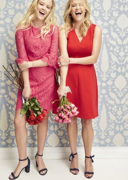 <p>The doppelgängers hug each other while gleaming and posing to the camera holding bunches of flowers.</p>