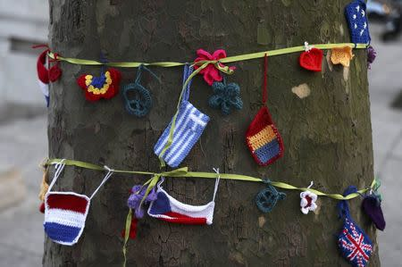 Knitted European flags hang from a ribbon tied around a tree during a protest in favour of amendments to the Brexit Bill outside the Houses of Parliament, in London