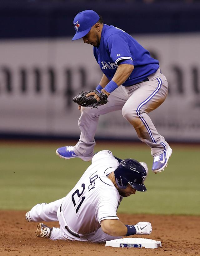 Toronto Blue Jays second baseman Maicer Izturis leaps over Tampa Bay Rays' James Loney after forcing Loney at second base on a fifth-inning fielder's choice by Rays' Desmond Jennings during a baseball game Monday, March 31, 2014, in St. Petersburg, Fla. (AP Photo/Chris O'Meara)