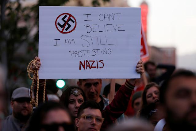 """<p>A demonstrator holds signs during a rally in response to the Charlottesville, Virginia car attack on counter-protesters after the """"Unite the Right"""" rally organised by white nationalists, in Oakland, California, U.S., August 12, 2017. (Stephen Lam/Reuters) </p>"""