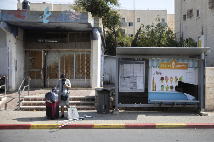 """An Israeli woman waits for a bus near a trashcan installed next to a bus stop that applauds to those who use it, in Jerusalem, Thursday, Oct. 14, 2021. Drop a piece of trash in, and a recording of a child's voice says """"Thank you very much!"""". (AP Photo/Sebastian Scheiner)"""