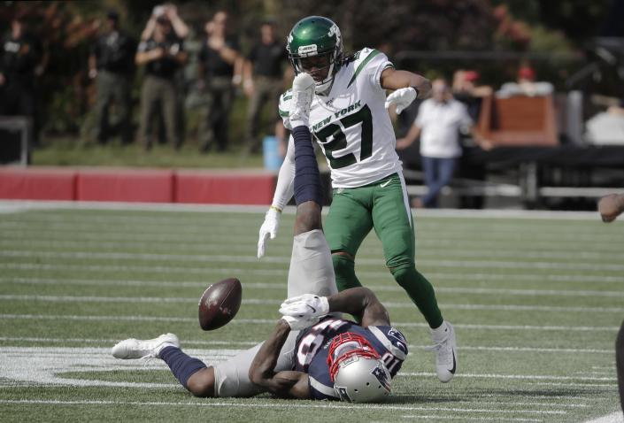 New England Patriots wide receiver Josh Gordon hits the turf while trying to catch a pass in front of New York Jets cornerback Darryl Roberts (27) during the first half of an NFL football game, Sunday, Sept. 22, 2019, in Foxborough, Mass. (AP Photo/Elise Amendola)