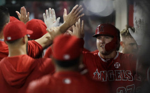Los Angeles Angels' Mike Trout, right, is high-fived in the dugout after his solo home run against the Chicago White Sox during the third inning of a baseball game Thursday, Aug. 15, 2019, in Anaheim, Calif. (AP Photo/Marcio Jose Sanchez)