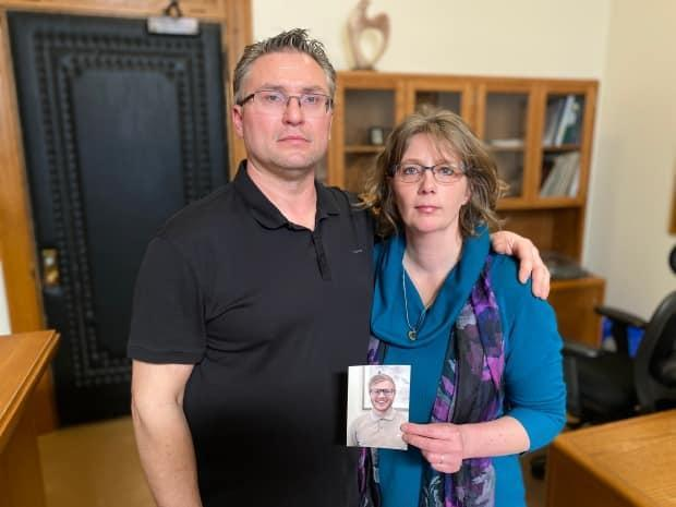 Carey Rigby-Wilcox and her partner Richard Wilcox show a photo of Steven Rigby. (Kirk Fraser/CBC - image credit)