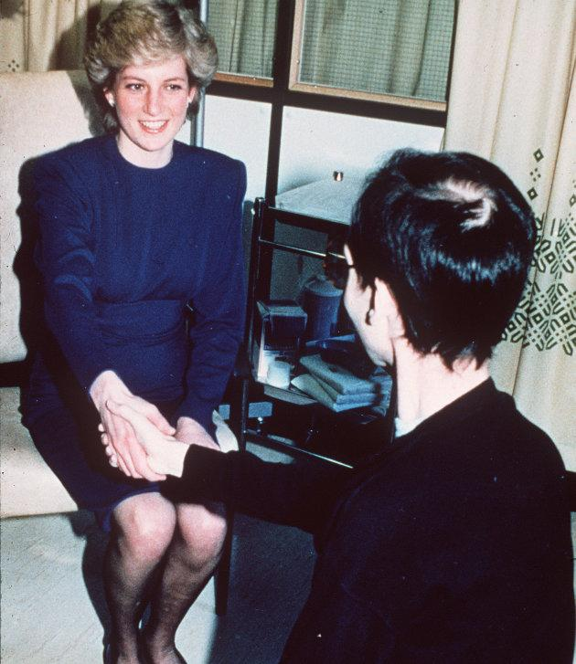 Diana, Princess of Wales, shakes hands with an AIDS victim as she opens a new AIDS ward at the Middlesex Hospital in April 1987 in London.