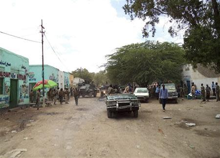 Somali government soldiers gather at the scene of a suicide bomb attack within a military base tea shop in Baladweyne
