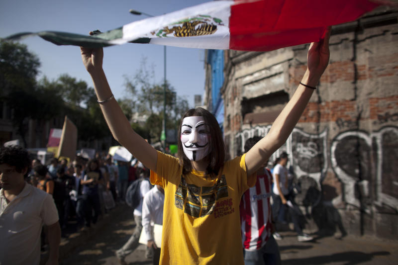 FILE - In this May 28, 2012 file photo, a demonstrator holds up Mexico's national flag during a protest against a possible return of the old ruling Institutional Revolutionary Party (PRI) in Mexico City. Students challenged presidential candidates to debates, urged others their age to pay attention to the campaign, and sought to fight off the return of the Institutional Revolutionary Party, which held power for 71 years until its ouster in 2000. Mexico will hold presidential elections on July 1. (AP Photo/Alexandre Meneghini, file)