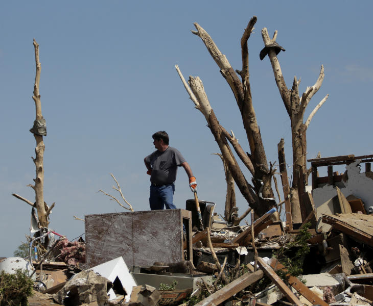 Kirk Guarnera takes a break from sorting through the rubble at his tornado-ravaged home Thursday, May 23, 2013, in Moore, Okla. Cleanup continues three days after a huge tornado roared through the Oklahoma City suburb, flattening a wide swath of homes and businesses. (AP Photo/Charlie Riedel)