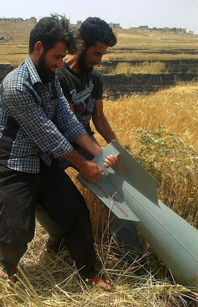 In this citizen journalism image provided by Edlib News Network, ENN, two Syrian men pull an unexploded rocket from a Syrian warplane in Idlib province, northern Syria, Monday, June 10, 2013. In Aleppo, activists said that rebels advanced inside the sprawling air base of Mannagh near the border with Turkey. The base has been under siege for months and rebels have been trying to capture it with no success. (AP Photo/Edlib News Network ENN)