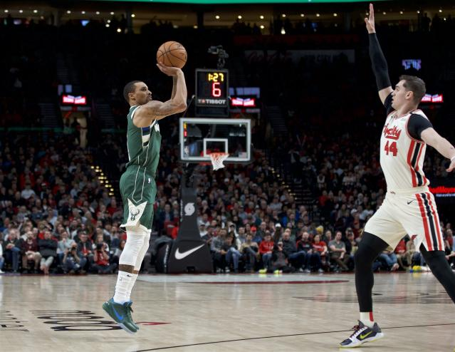 Milwaukee Bucks guard George Hill, left, shoots in front of Portland Trail Blazers forward Mario Hezonja during the second half of an NBA basketball game in Portland, Ore., Saturday, Jan. 11, 2020. (AP Photo/Craig Mitchelldyer)