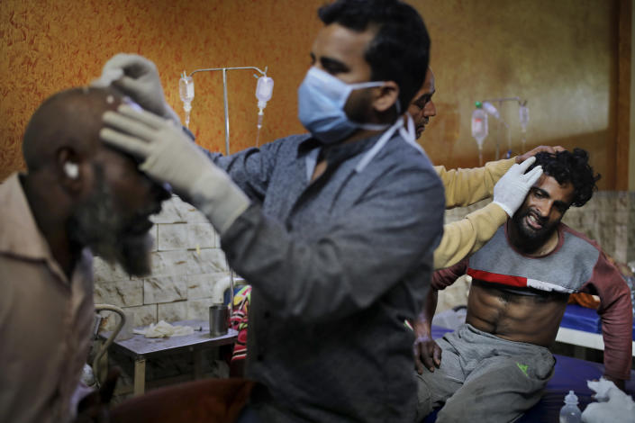 FILE - In this Friday, Feb. 28, 2020 file photo, paramedics tend to the wounds of Mehfooz Umar, left, and Mohammad Afzal at Al-Hind hospital in Old Mustafabad neighborhood of New Delhi, India. As the first anniversary of bloody communal riots that convulsed the Indian capital approaches, Muslim victims are still shaken and struggling to make sense of their struggle to seek justice. Many say they have run repeatedly into a refusal by police to investigate complaints made by Muslims against Hindu rioters. (AP Photo/Altaf Qadri, File)