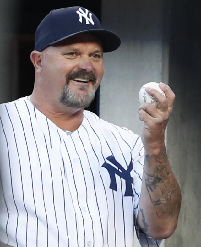 Former New York Yankees stating pitcher David Wells shows the ball from the dugout before throwing out the ceremonial first pitch before a baseball game between the Yankees and the Minnesota Twins in New York, Monday, April 23, 2018. Well pithed a perfect game against the Twins at Yankee Stadium in May 17, 1998. (AP Photo/Kathy Willens)