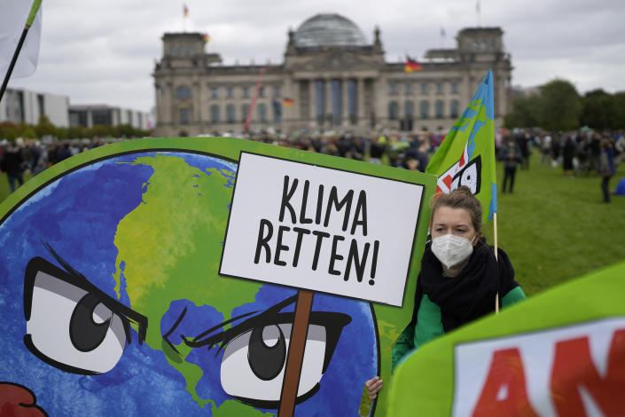 """An activist holds a banner saying """"Save the Climate"""", during a Fridays for Future global climate strike in Berlin, Germany, Friday, Sept. 24, 2021. (AP Photo/Markus Schreiber)"""