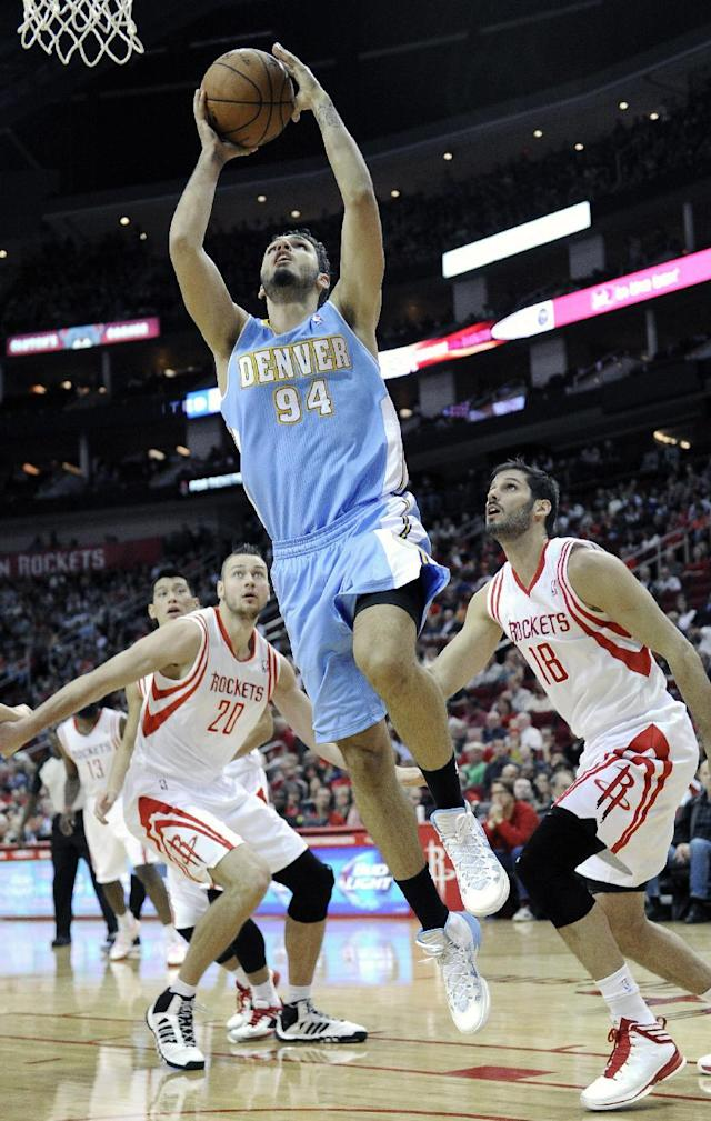 Denver Nuggets' Evan Fournier (94) goes to the basket between Houston Rockets Donatas Motiejunas (20) and Omri Casspi (18) in the first half of an NBA basketball game Saturday, Nov. 16, 2013, in Houston. (AP Photo/Pat Sullivan)
