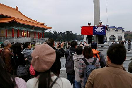Tourists attend a flag-lowering ceremony at Chiang Kai-shek Memorial Hall in Taipei, Taiwan January 22, 2019. Picture taken January 22, 2019. REUTERS/Tyrone Siu