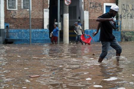 A man walks through a flooded street after heavy rains in Vila Prudente neighbourhood in Sao Paulo, Brazil March 11, 2019. REUTERS/Amanda Perobelli