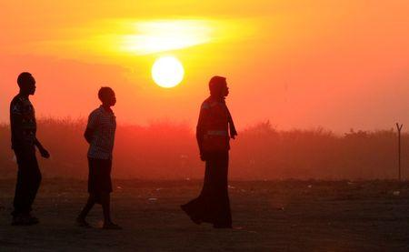FILE PHOTO: People who fled fighting in South Sudan are seen walking at sunset on arrival at Bidi Bidi refugee's resettlement camp near the border with South Sudan, in Yumbe district, northern Uganda December 7, 2016. REUTERS/James Akena