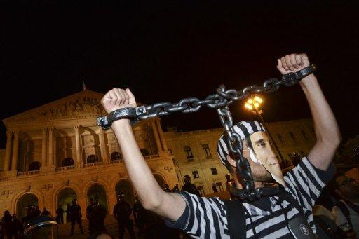 <p>A man dressed as a a prisoner and wearing a mask representing Portuguese Prime Minister Pedro Passos Coelho takes part in a protest in front of the Portuguese parliament. Mass protests in Spain and Portugal, against ever tougher austerity measures, have ramped up the pressure on Iberian governments struggling to avoid international bailouts.</p>